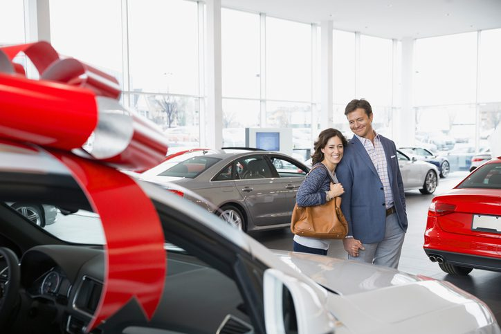 Gill Insurance | Couple shopping in car dealership showroom